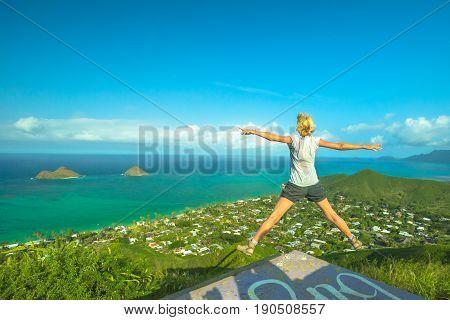 Lanikai Pillbox Hike. Hawaiian hiking enjoying. Joyful carefree hiker jumping. Happy woman celebrates one of most spectacular Oahu hiking trails in Hawaii over Lanikai Beach and Mokulua Islands.