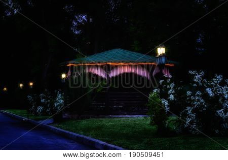 A gazebo for relaxation is decorated with a bright glowing LED tape very beautiful at night around shine lights