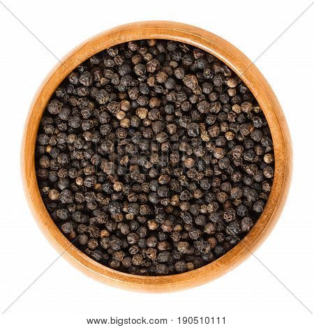 Black pepper in wooden bowl. Dried berries of Piper nigrum are called peppercorns. Made from the unripe drupes of the pepper plant. Spice and seasoning. Isolated macro food photo close up over white.