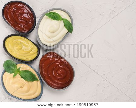 Top view of classic sauces set in trendy plates on white concrete background. Sauces set - salsa, mustard, ketchup, mayonnaise, cheese sauce, and basil for serve. Flat lay. Copy space.