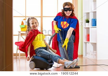 Kid girl and her mother weared Superhero costumes. Cute helper child and woman make cleaning room and have a fun pastime.