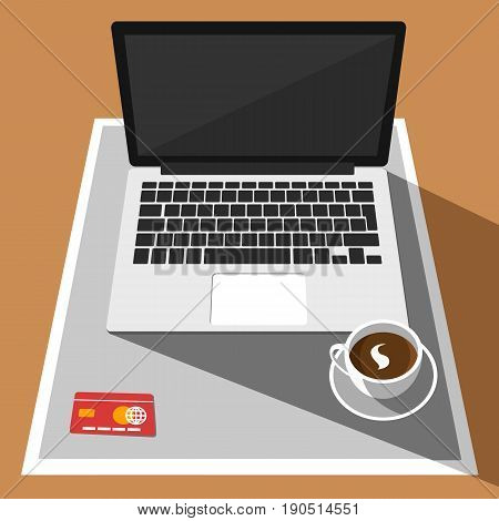 Overhead view of laptop, credit card and a cup of coffee on a desk. Business concept