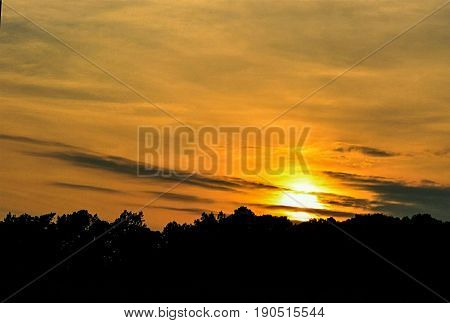 A beautiful dark golden sunset silhouette with sharp cloud formations.