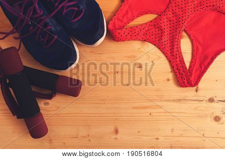 Sports and fitness accessories: dumbbells, sneakers and sports bra. Healthy lifestyle concept.