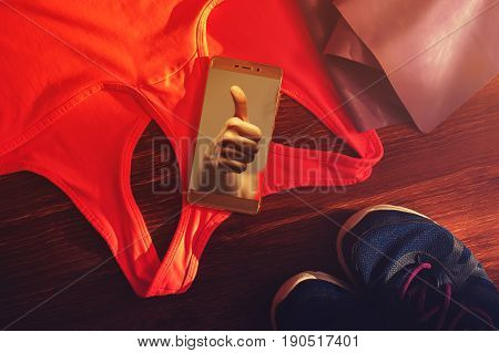 Sports and fitness accessories: resistance band, sneakers, smartphone and sports bra. Healthy lifestyle concept.