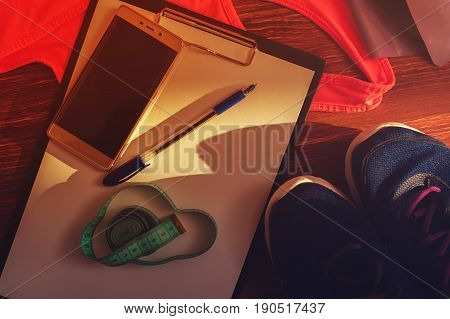 Sports bra, sneakers, measuring tape and blank clipboard with pen. Sports and fitness equipment. Weight loss and healthy lifestyle concept.