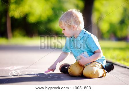 Concentrated Little Kid Boy Sitting And Drawing With Colored Chalk On Asphalt