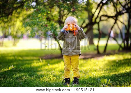 Little Boy Taking Picture Using Photo Camera In Summer Park