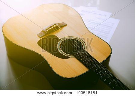 Closeup acoustic guitar laying across sheet music