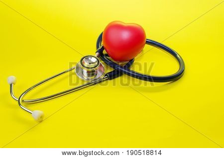 red heart and stethoscope on yellow background heart health care and medical technology concept selective focus copy space