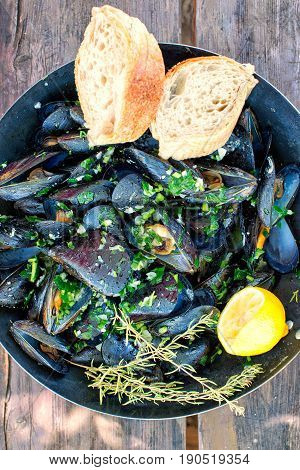 gourmet mussels served on a pan and a wooden plank with fresh herbs for a tasty seafood meal