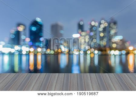 Opening wooden floor Twilight blurred bokeh city office building with water reflection night view abstract background