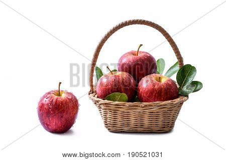 Fresh red apples with drops of water and green leaves packed in rattan basket isolated on white background