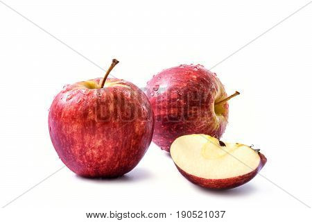 Two red apples (Malus domestica Malus pumila or Pyrus malus) with drops of water and a quarter of fresh apple with seeds isolated on white background