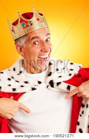 senior man wearing a king's robe and crown, pointing at his white t-shirt