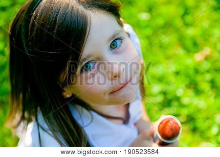 a 6-year old girl is hold some ice cream and looking up at the camera.