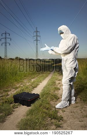 Criminologist technician dressed to disposable overall and protective equipment