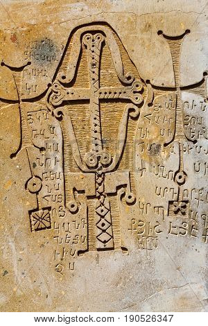 Christian carved bas-relief. On the stone placed the ornament with the Christian cross and the Armenian text.