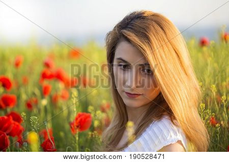 Portrait of upset blonde woman standing on field of poppies