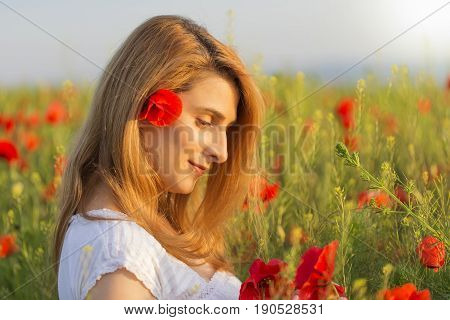 Woman in white dress in a full field of poppies