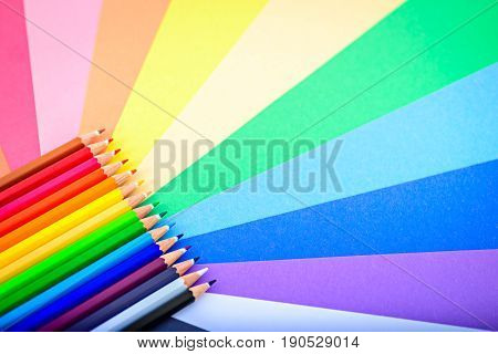 Close up macro shot of sharp colorful pencils on multicolored paper background