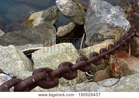 Big rusty chain locked inside the rocks