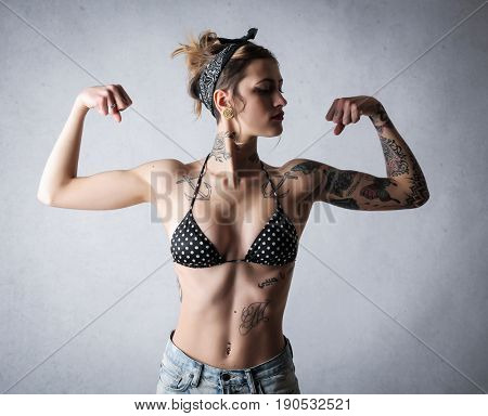 Tattooed woman showing her muscles