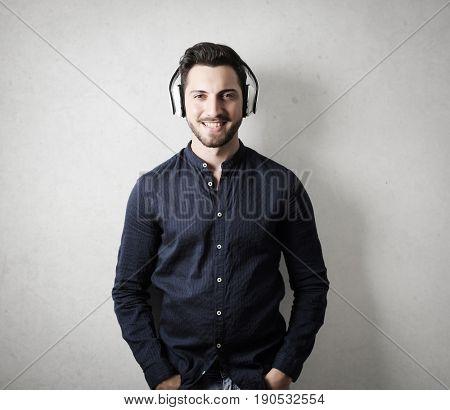 Smiling handsome man listening to music through headphones