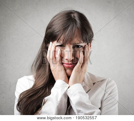 Sad woman holding her face between her hands
