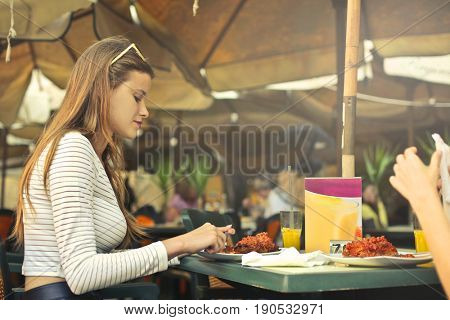 Girls sitting outdoors at the cafe