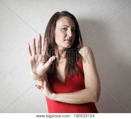 Annoyed woman showing a stop gesture with her hand