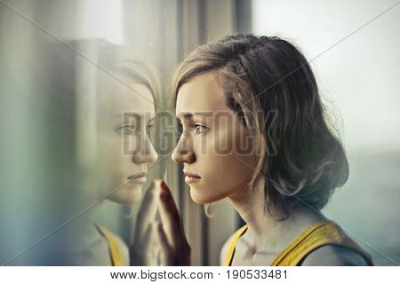 Sad girl looking out of the window