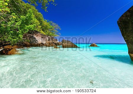 Summer landscape sea coast with crystal clear water and white sand. On the background of humpback rocks.