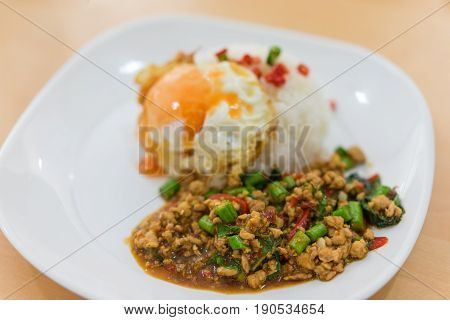Rice topped with stir-fried pork and basil and fired egg. Selective focus pork Popular Thai food