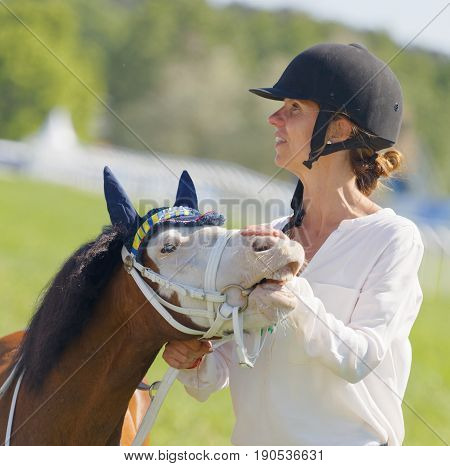 STOCKHOLM SWEDEN - JUNE 06 2017: Woman strokes a cute pony gallop race horses on the muffle at Nationaldags Galoppen at Gardet. June 6 2017 in Stockholm Sweden
