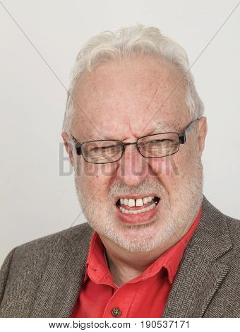 Angry senior with glasses bares his teeth - on bright background