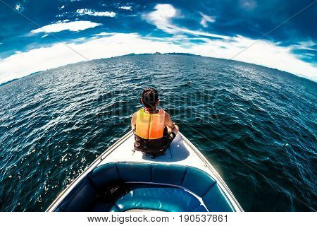 Man in life orange life jackets sit on speed boat front view lonely man