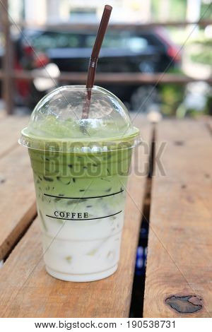Plastic cup of Iced matcha with brown straw on table