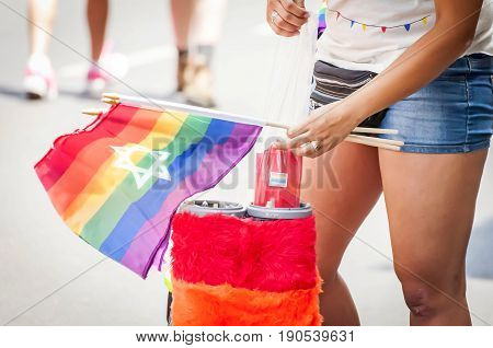 TEL AVIV, ISRAEL. June 9, 2017. Girl selling LGBT rainbow flags in the street due to the Gay Pride Parade in Tel Aviv 2017.