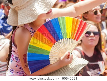 TEL AVIV, ISRAEL. June 9, 2017. Unknown little girl - participant of the Tel Aviv Gay Pride parade 2017 holding a multicolored LGBT paper fan.