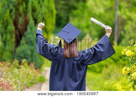 Young woman graduate put her hands up and celebrating with certificate in her hand and feeling so happy.