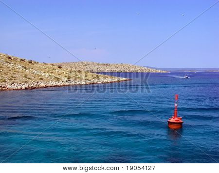 Red buoy floating near rocky islets in colourful sea