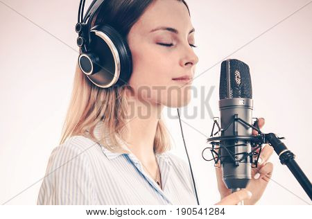 Female Voice Talent in the Recording Studio. Closeup Photo. Girl Recording Her Voice Using Professional Microphone