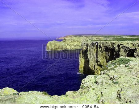 Eroded cliff coastline on deep blue ocean