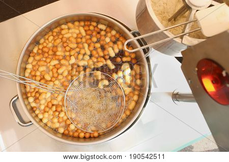Sweet mini donuts frying in oil. Pot with mini donuts and colander. Donuts machine top view.