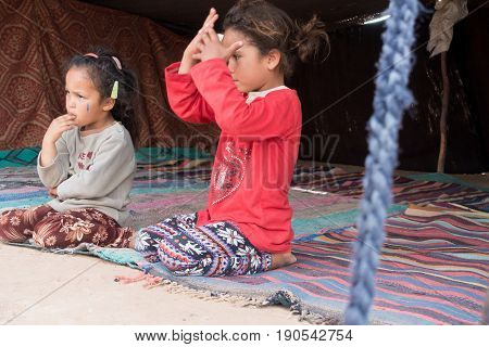 Merzouga Desert Morocco - May 09 2017: Two young Moroccan Berber girls sitting in a Berber tent in the Sahara desert.