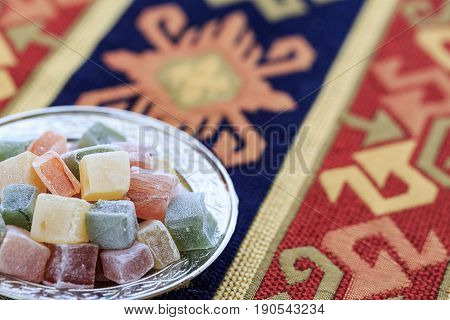 Turkish delights in plate on the traditional turkish carpet