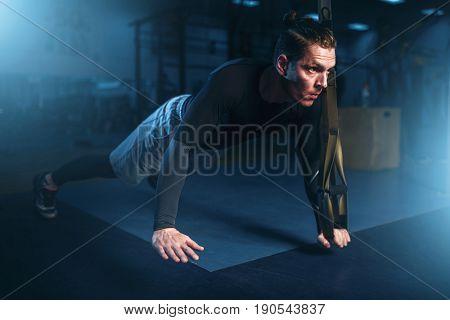 Athlete on training, pushup exercise with rope
