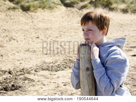 Young boy leaning on a post and gazing into the distance at the beach.