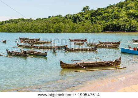 Traditional wooden dugout rowing outrigger canoes on Nosy Be island Madagascar